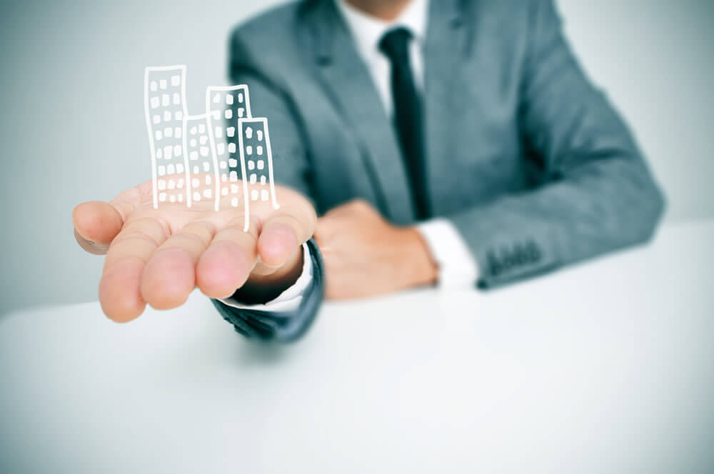 cartoon office block on man's outstretched palm